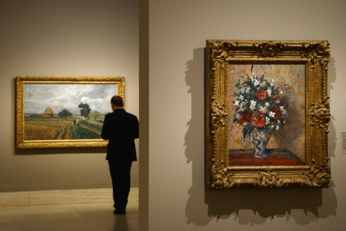 "A man looks at the painting ""The old road to Ennery at Pontoise"" (L) by Camille Pissaro (R) next to the painting ""Still life with peonies and Mock orange"" during the opening of the first monographic exhibition in Spain on Danish-French impressionist painter Camille Pissarro at the Thyssen-Bornemisza museum in Madrid, on June 3, 2013. AFP PHOTO / DOMINIQUE FAGET."